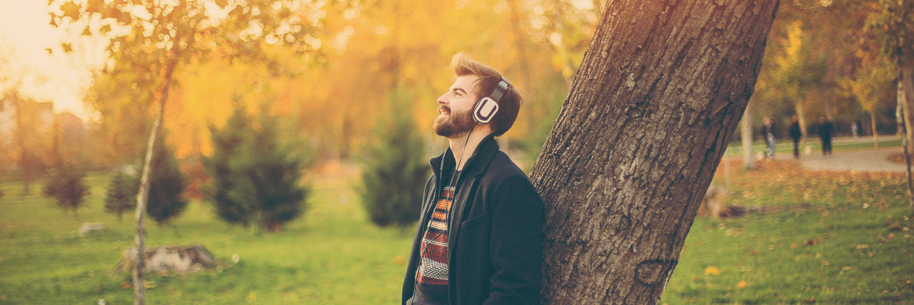 Man with headphones leaning on a tree in park.