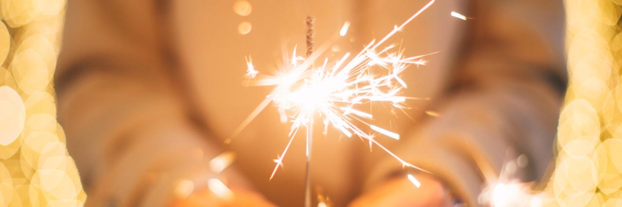 A woman holding a sparkler.