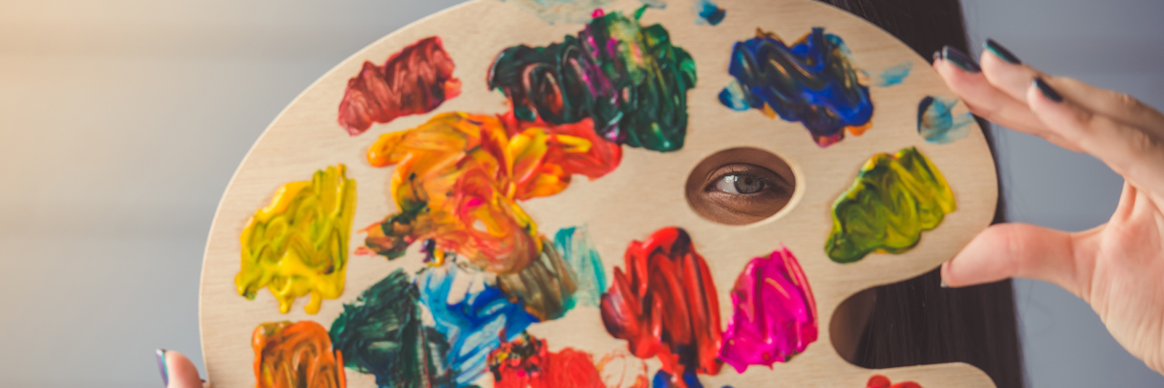 A woman holding an art easel to her face, which has paint on it.