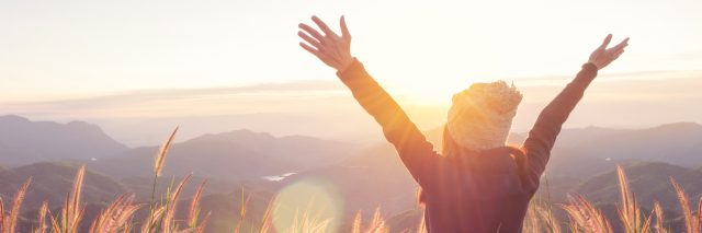 Carefree Happy Woman Enjoying Nature on grass meadow on top of mountain cliff with sunrise. Beauty Girl Outdoor. Freedom concept. Len flare effect. Sunbeams. Enjoyment.
