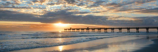 Beautiful sunrise over ocean horizon and pier.