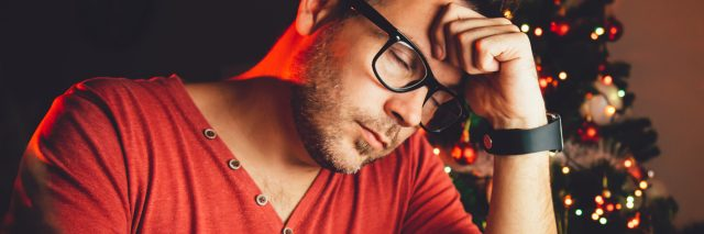 man in red shirt in front of computer at Christmas depression tired