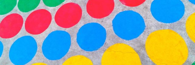 A homemade Twister game of colorful circles on the ground.