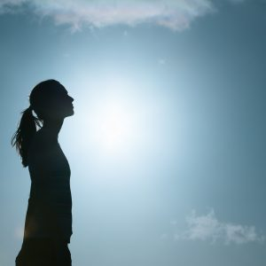 silhouette of woman against the blue sky