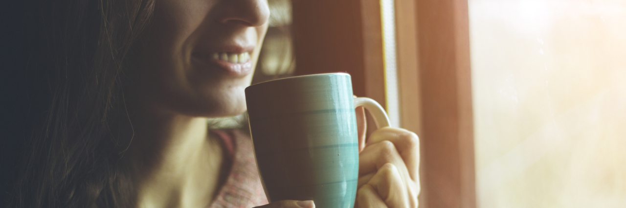 woman sitting next to a window drinking coffee during winter