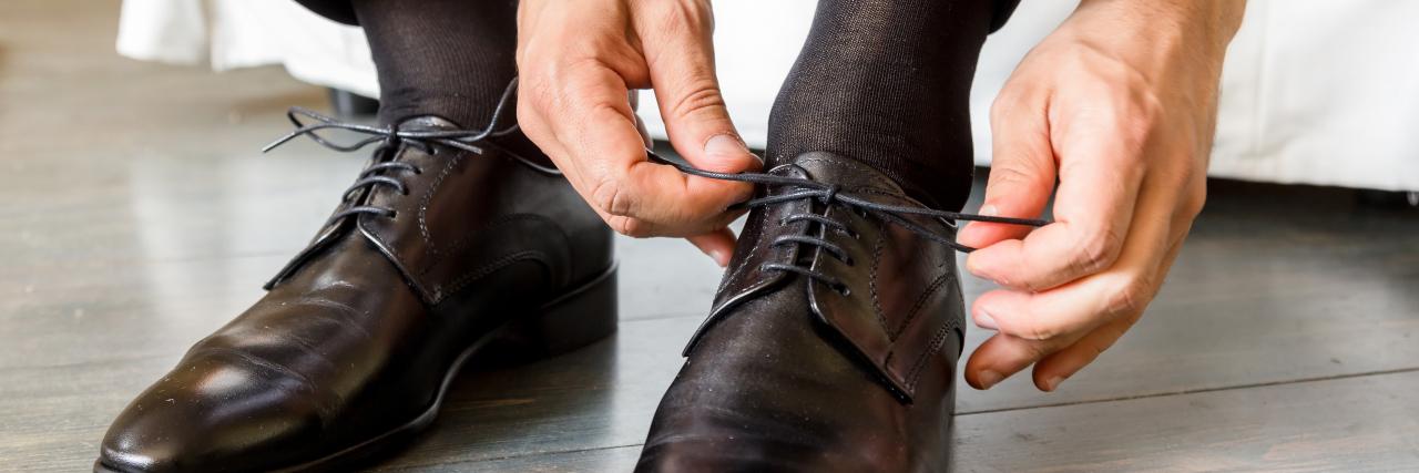 Businessman laces his shoes.