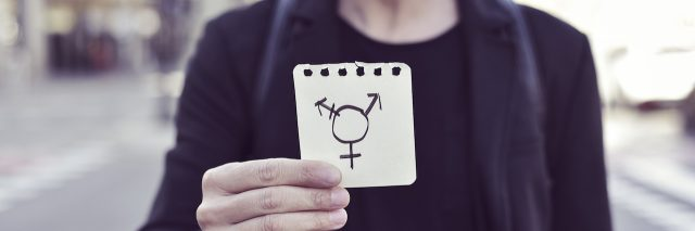 A man holding up the transgender symbol