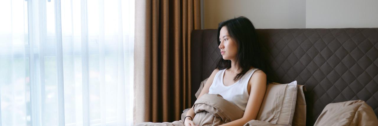 sad depressed woman thinking on bed in luxury bedroom