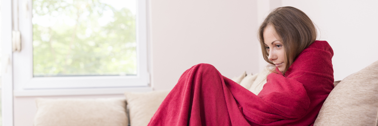 Young woman sitting on a couch covered with blanket, having a fever.
