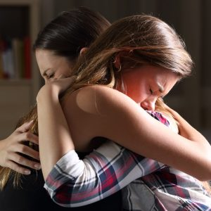 side view of two young women embracing and crying