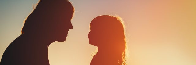 Silhouette of happy mother and little daughter at sunset.