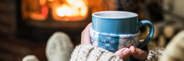 woman sitting with a mug and a blanket in front of the fire
