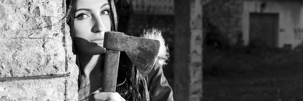 black and white photo of woman with axe behind wall