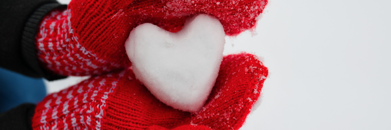 woman wearing red gloves and holding a heart of snow