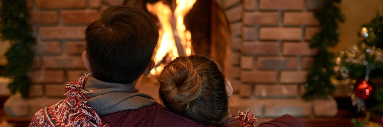 husband and wife around a christmas fire