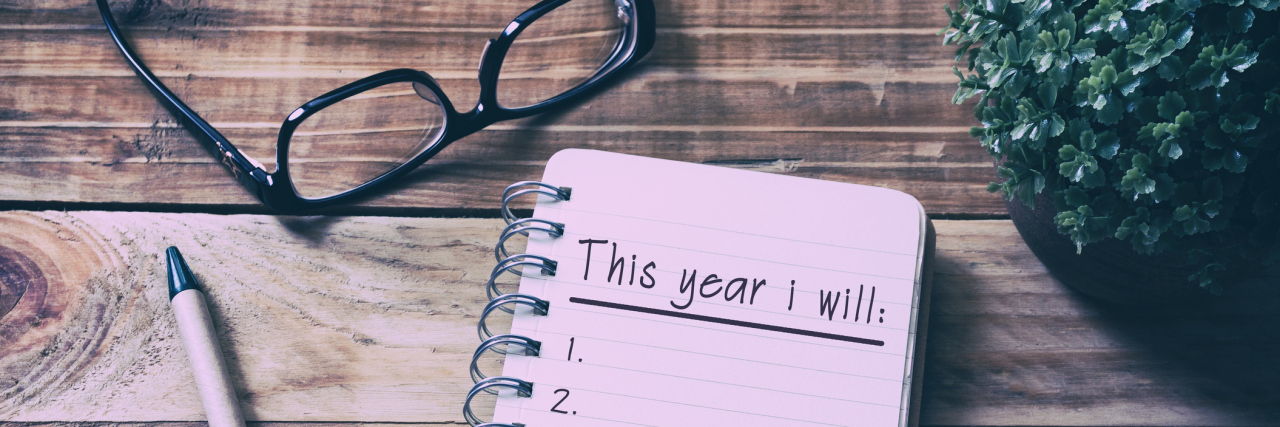 new year's resolutions on notepad sitting on wooden table