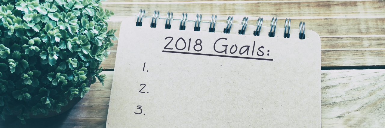 "picture of a notebook and pen. on the paper ""2018 goals"" is written."