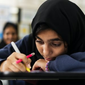 young muslim student leaning on desk looking depressed