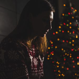 woman sitting next to a christmas tree in the dark looking upset