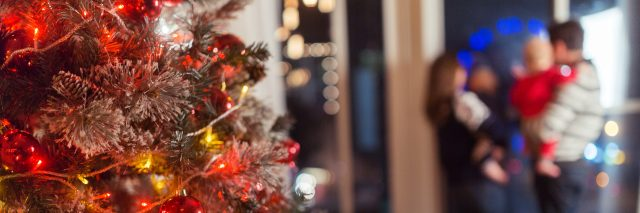 Christmas scene with happy family of four, tree gifts and window in blurred bokeh background, copy space