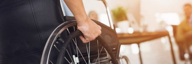 Man sitting in a wheelchair. He holds his hands on the wheel.