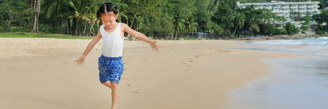 Little Asian girl running on the beach.