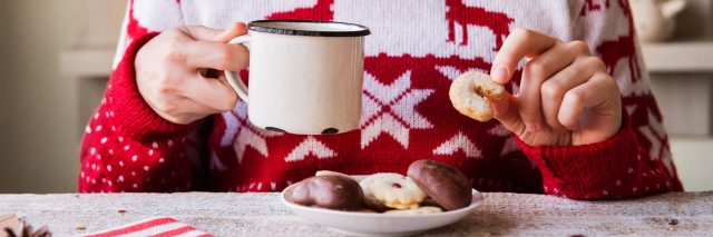woman wearing a christmas sweater and holding a mug and a cookie