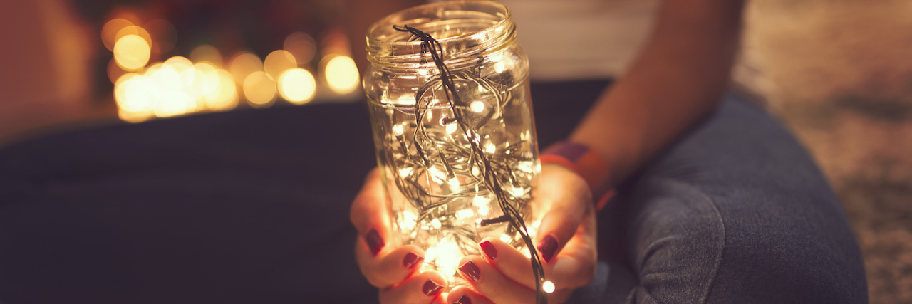 Woman holding a jar full of lights