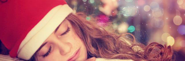 Teen girl sleeping near Christmas tree