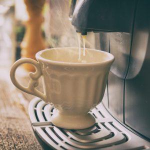 A coffee machine pouring hot liquids into a coffee mug.