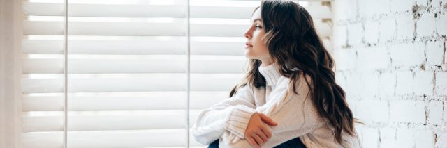 young woman at home sitting by window at christmas