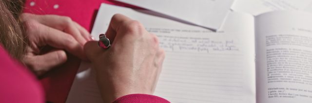 Woman hand writing or signing in a document on a desk at home or office