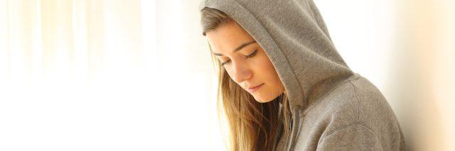 pensive teen looking down indoors wearing a white hoodie