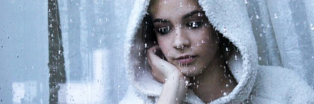 contemplative young woman at rainy window with hot drink