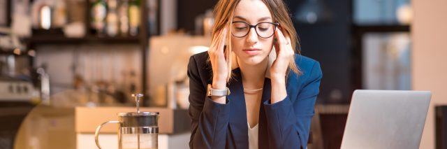 businesswoman in cafe with laptop looking stressed