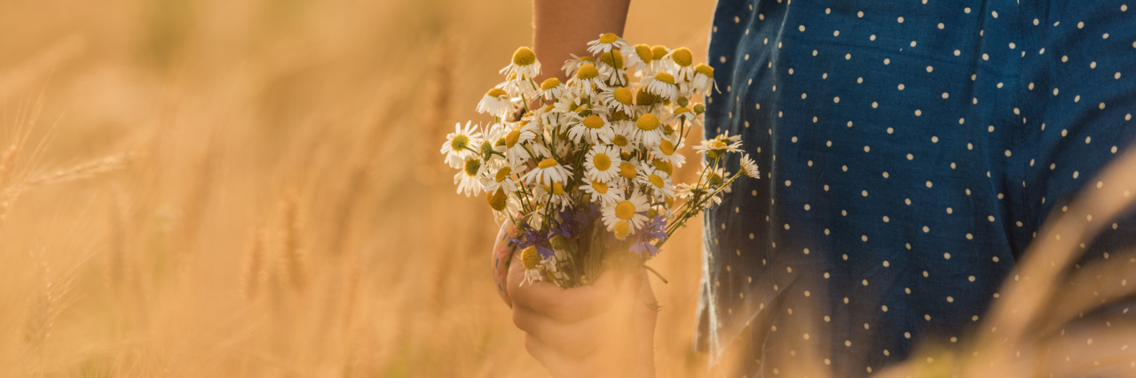 young woman in wheat field with daisy bouquet of flowers