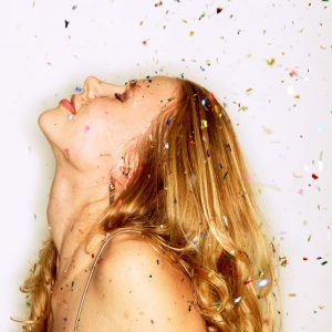 A photo of a woman looking up towards falling confetti.