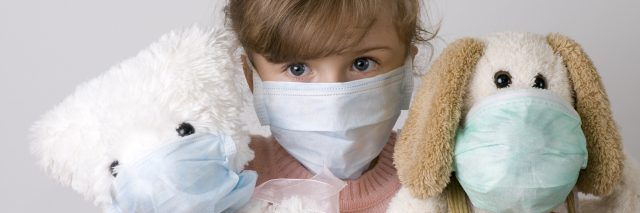 A little girl and her toys wearing medical masks.