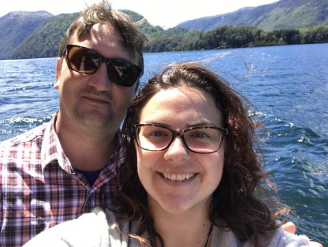 The writer and her husband in front of a body of water.