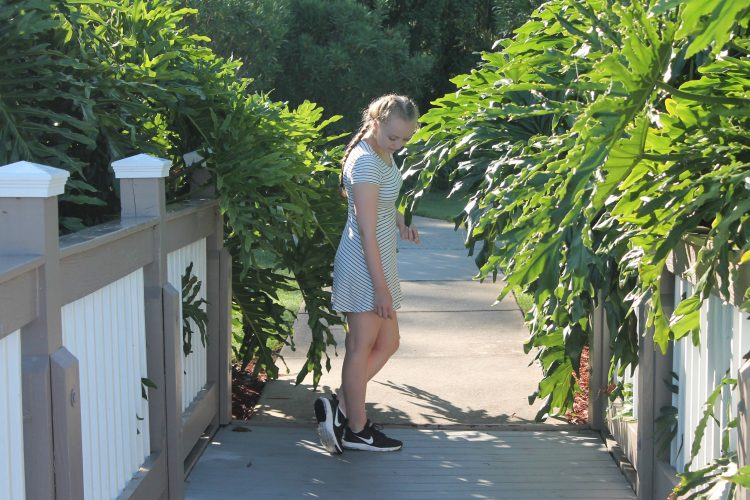woman standing on a path outside between plants