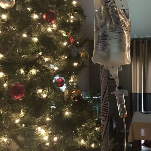 An IV pole and bag in front of a Christmas tree.