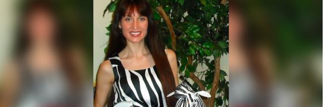woman in a zebra print dress holding a stuffed zebra and medical supplies