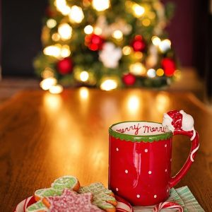 Christmas cookies and a coffee mug in front of a lit-up Christmas tree.