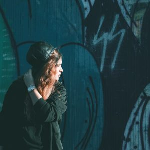 young woman in front of street art wall looking off into distance