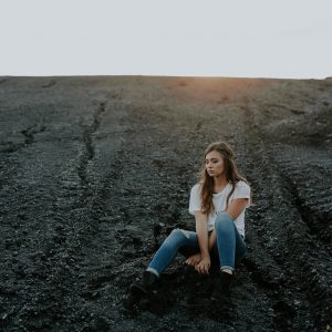 woman alone on beach or rocky ground