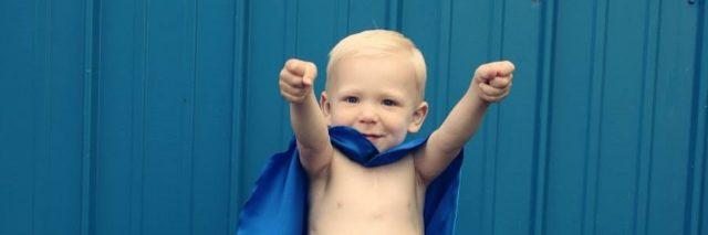 Little boy with blue super hero cape