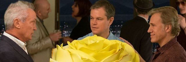 """A photo of the movie """"Downsizing,"""" with Matt Damon holding a large rose that is bigger than him."""