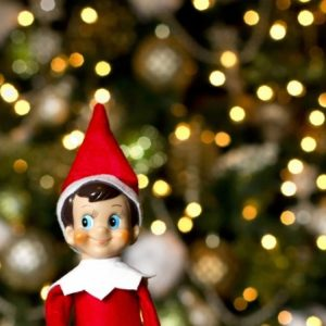 Elf on the shelf. Toy elf in red and white suit and Santa hat with Christmas tree in background.