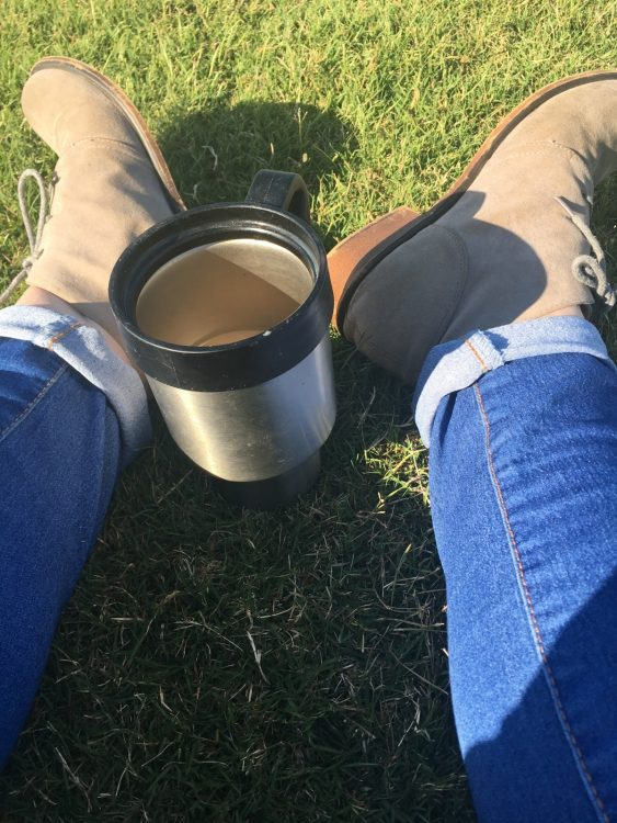 photo of woman's feet and a cup of coffee