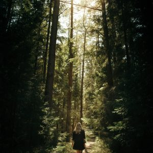 young woman walking along path through forest